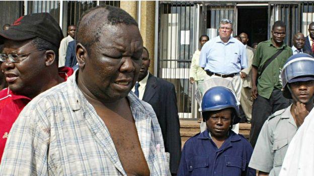 """Nyuma yo kunanirwa kubona amajwi ahagije yari gutuma amatora atajya mu cyiciro cya kabiri aho yari ahanganye na Morgan Tsvangirai, Mugabe yagaragaje ko ibyo ntacyo bimubwiye, ko """"Imana yonyine"""" ari yo yamukura ku butegetsi. Kubera ibyo, kandi bitewe n'ibikorwa by'urugomo byakorwaga n'abayoboke b'ishyaka riri ku butegetsi, Bwana Tsvangirai yakuyemo ake karenge, arazibukira. Kuri iyi foto, agaragara ageze ku bitaro agiye kuvurwa ibikomere yakuye muri 'mitingi' y'ishyaka rye mu 2007."""