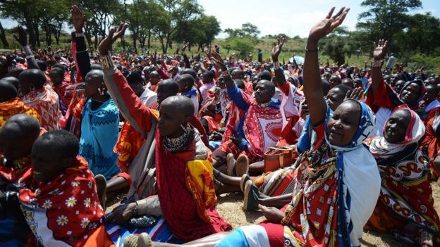 Kenyan Maasai women raise their hands as they gather during a meeting dedicated to the practice of female genital mutilation on June 12, 2014, in Enkorika, Kajiado, 75km from Nairobi.
