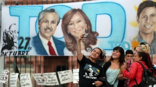 Pessoas tiram foto diante de faixa de Alberto Fernández e Cristina Fernández