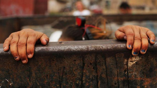 Manos de una niña sobre un cerco en América Latina