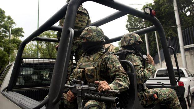Efectivos de la Marina mexicana patrullan las calles en camioneta.