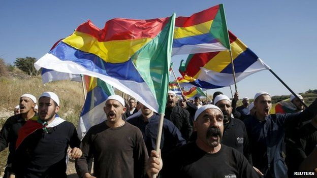 Druze men hold up Druze flags at a protest in the Israeli-occupied Golan Heights (16 June 2015)