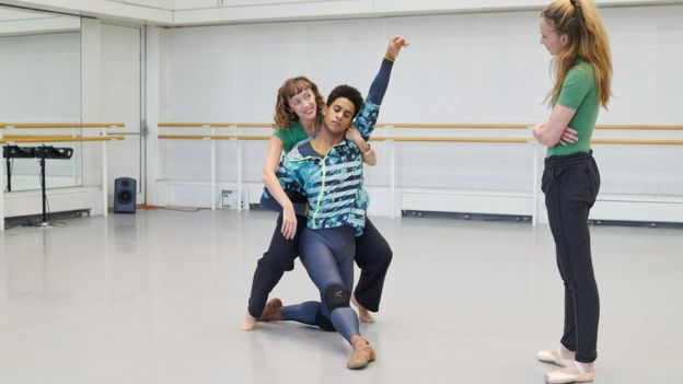Choreographer Cathy Marston behind Marcelino Sambé, shows Lauren Cuthbertson how to hold her cello during rehearsal