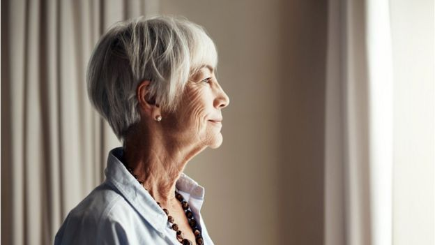 Mujer mayor mirando por la ventana