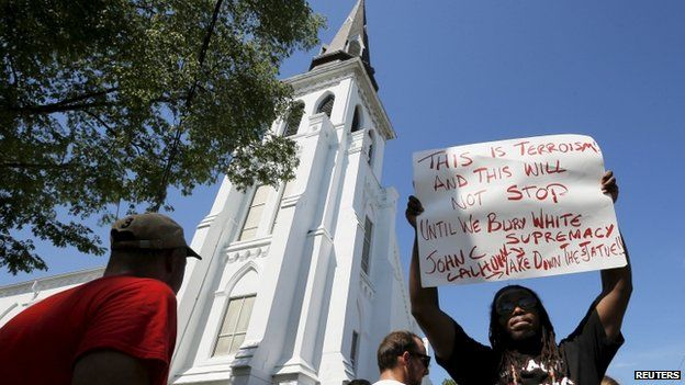 A man holds a protest sign outside the Emanuel African Methodist Episcopal Church, where a mass shooting took place, in Charleston, South Carolina 20 June 2015.