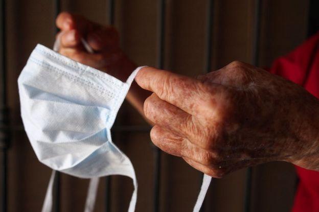 Manos de anciana sosteniendo una mascarilla