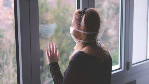 Mujer con máscara mira la ventana con la mano en el cristal