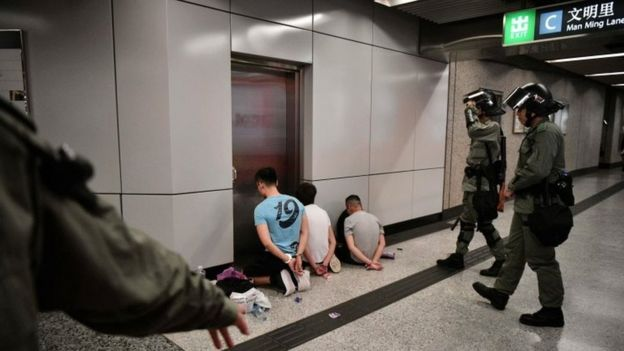 Suspected protesters kneel on the ground at a Hong Kong metro station as police guard them