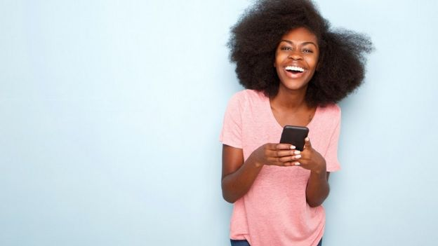 Девушка пишет текстовые сообщения и смеется