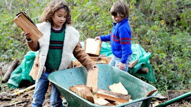 Crianças recolhem pedaços de madeira