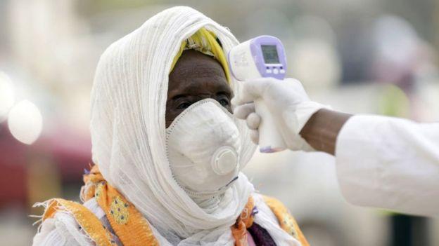 Des agents de santé prennent la température des fidèles avant qu'ils n'entrent dans l'église à Addis-Abeba, juin 2020