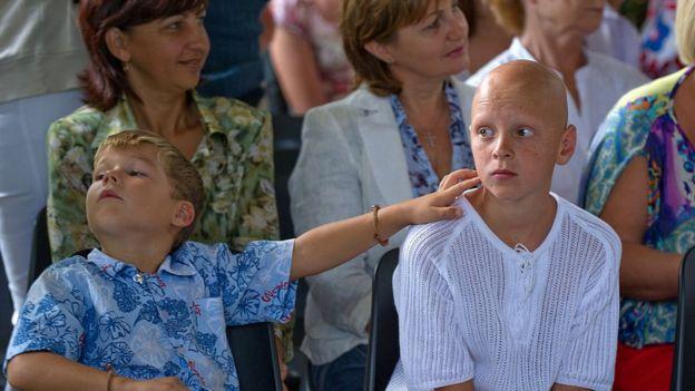 Duas crianças sentadas, pacientes do projeto cubano, participam de evento