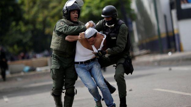 Miembros de las fuerzas de seguridad de Venezuela arrestan a un manifestante opositor