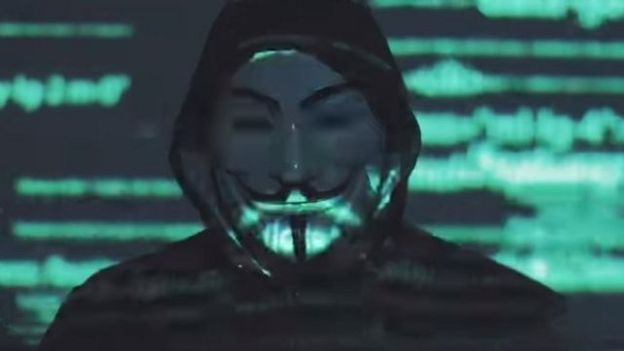 A man in a Guy Fawkes mask appears in this image taken from a Facebook video