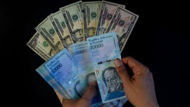 Dólares y bolívares venezolanos.