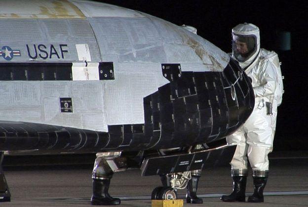 Técnicos en trajes protectores examinan el X-37B