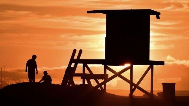 Duas pessoas sentadas na praia ao lado de um posto salva-vidas enquanto o sol se põe