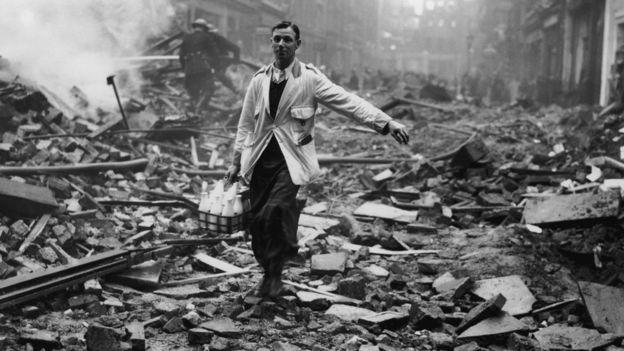 A milk delivery boy on a street in London bombed in World War II.