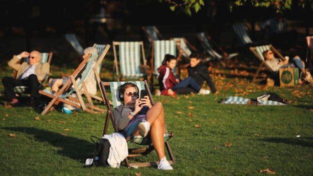 parkta güneşlenen insanlar