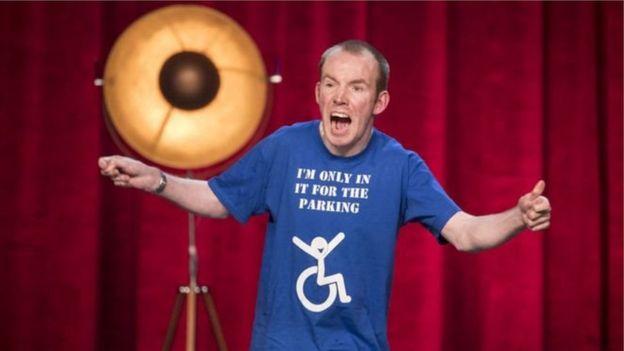 Diễn viên hài The Lost Voice Guy mặc áo phông với dòng chữ gây cười về khuyết tật của mình.