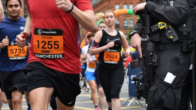 Armed police watch over runners close to the starting line during the Simplyhealth Great Manchester Run