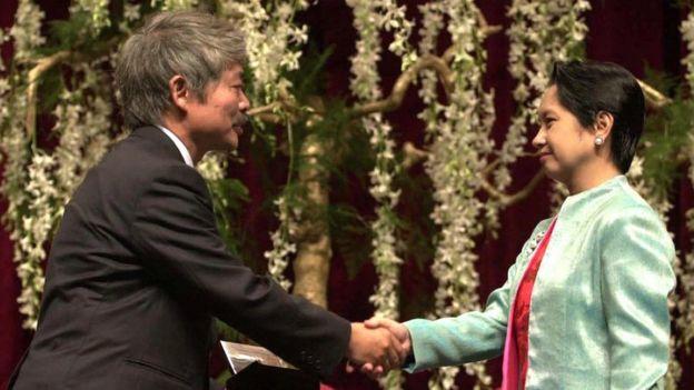 Then-Philippine president Gloria Arroyo (R) congratulating Tetsu Nakamura (L),