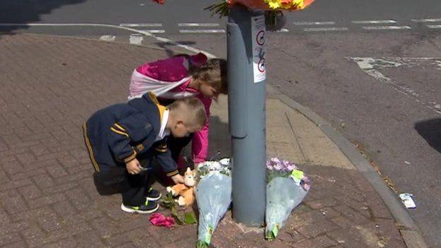 Children putting down flowers
