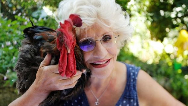 Corinne Fesseau poses with her rooster Maurice