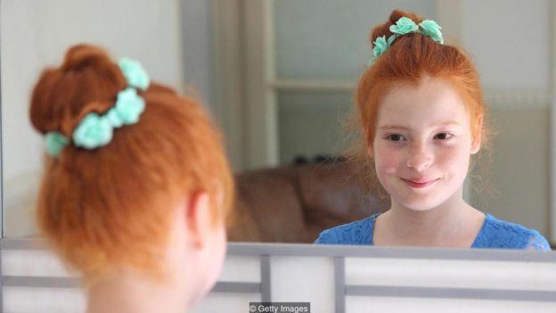 Menina sorri diante do espelho