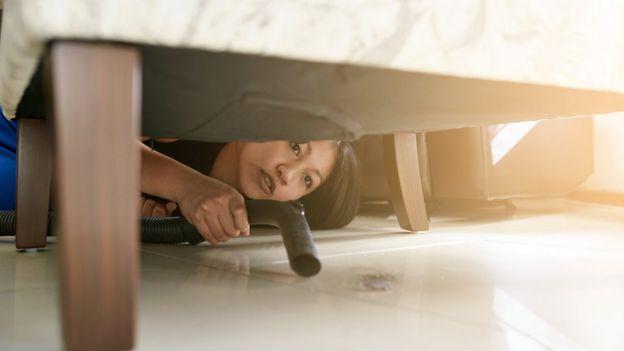 Mujer aspirando debajo de la cama