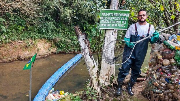 Diego segurando uma rede em frente ao rio e barreira que criou