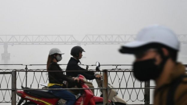Motorists wearing face masks ride o­n the Long Bien bridge amidst a blanket of smog over Hanoi o­n March 28, 2018