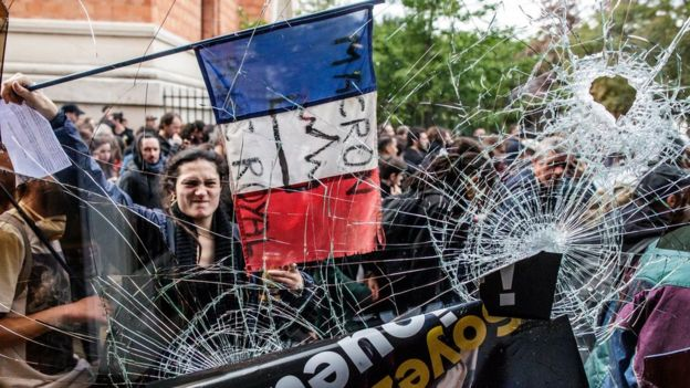 A protester holds the French Tricolour with an anti-Macron slogan outside a destroyed McDonald's
