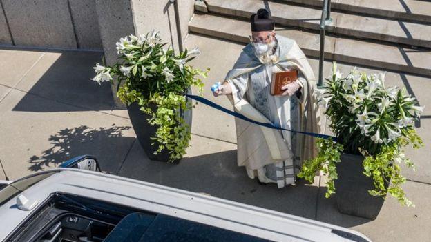 Un sacerdote rocía agua bendita con una pistola de agua.
