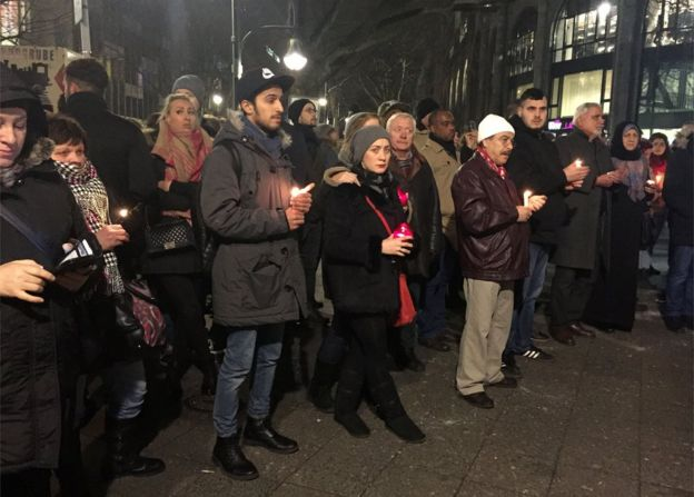 People hold candles close to the scene where a truck ploughed into a crowded Christmas market outside the Kaiser Wilhelm Memorial Church in Berlin, 20 December