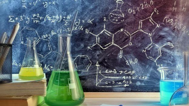 Quadro negro com fórmulas, vidros com experimentos e canetas representam disciplinas de ciências