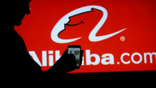 Man with the Alibaba app on the phone.
