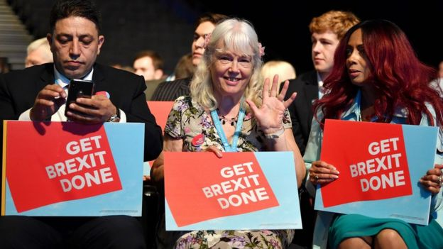 """Delegates at Conservative Party Conference holding """"Get Brexit Done"""" signs"""