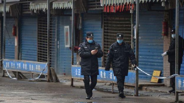 Nhân viên bảo vệ tuần tra bên ngoài chợ hải sản Huanan ở Vũ Hán - nơi phát xuất chủng virus corona mới