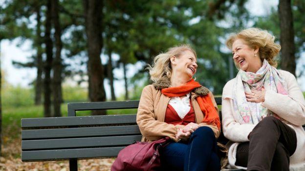 Dos mujeres sonriendo en un banco.