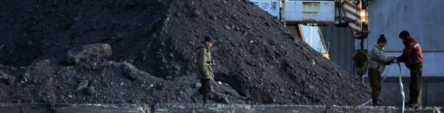 North Korean labourers work beside the Yalu River at the North Korean town of Sinuiju on February 8, 2013 which is close to the Chinese city of Dandong. Piles of coal are seen.