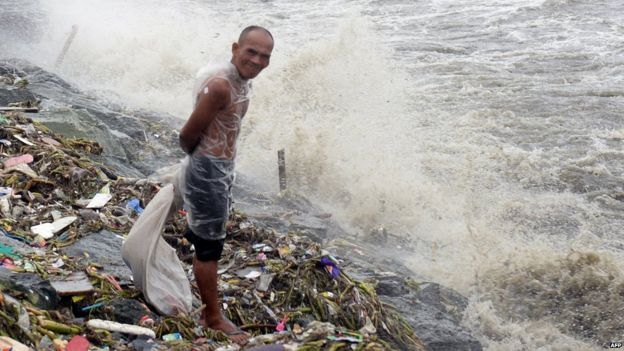 A map stands on the Manila coast amid rain brought on by Typhoon Koppu