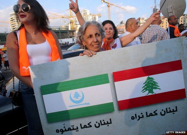 """Supporters of Lebanese Christian leader Michel Aoun's opposition Free Patriotic Movement (FPM) hold a placard reading in Arabic """"Lebanon as we see it"""" (R) and """"Lebanon how they wish it to be"""""""