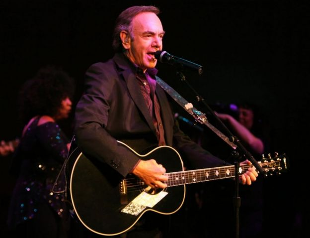 Neil Diamond pictured performing with a guitar in 2008