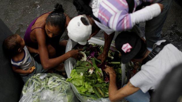 Personas en Venezuela buscan comida en la basura.