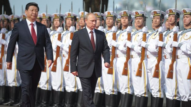 Xi Jinping and Vladimir Putin walk by Chinese troops at a military ceremony in 2014