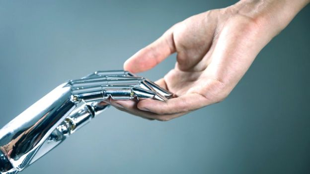 Image of a robotic hand and a human joining.