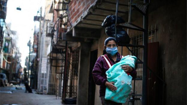 Mulher com máscara e bebê na Villa 31, um dos bairros mais afetados pela pandemia em Buenos Aires