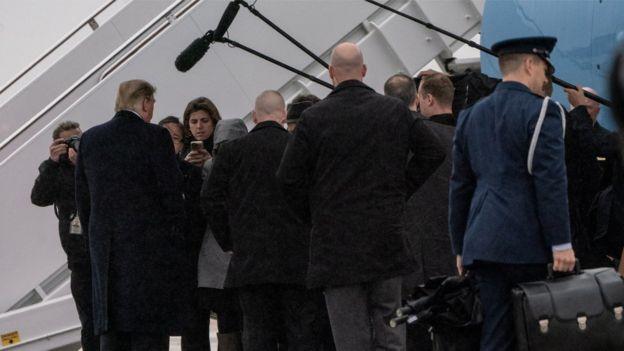 Donald Trump de espaldas siendo entrevistado por periodistas en la pista de un aeropuerto.