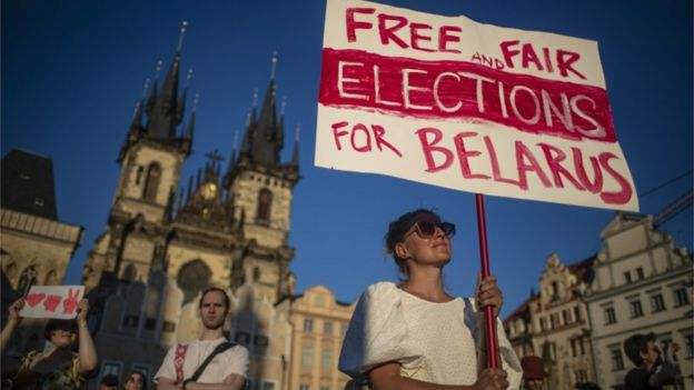 A protester holds a sign that reads 'Free and fair elections for Belarus' in the Czech capital Prague